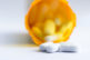 pill bottle close up of a group of white tablets with an out of focus prescription bottle in the background